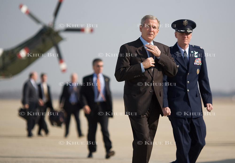 Pres. Bush jokingly adjusts his tie as he boards AF-1 Tuesday, March 20, 2007.  <br /> <br /> Photo by Khue Bui