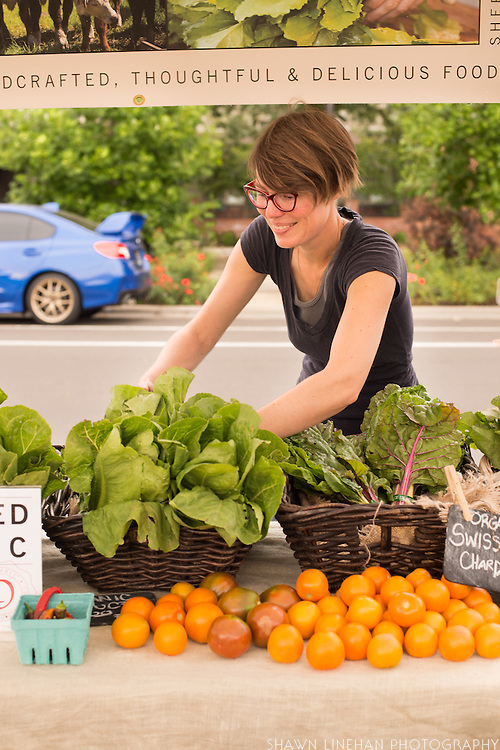 Dawn, one of the farmers at Our Table Cooperative, arranges produce for the Wilsonville Farmers Market Booth.