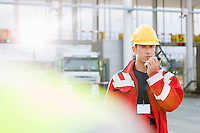 Mid adult worker using walkie-talkie in shipping yard