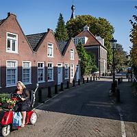 Nederland, Amsterdam, 15 oktober 2017.<br /> Sloten is een dorp en de naam van een voormalige gemeente in de Nederlandse provincie Noord-Holland. Sloten ligt in het zuidwesten van de stad Amsterdam als onderdeel van het stadsdeel Nieuw-West. Sinds 1962 is er een Dorpsraad Sloten-Oud Osdorp.<br />  Sloten - dat wordt een beschermd dorpsgezicht.<br /> Op de foto: De Sloterweg door Oud sloten met op de achtergrond de Katholieke kerk toren.<br /> <br /> <br /> Foto: Jean-Pierre Jans