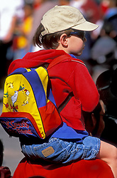 Stock photo of a young boy with a backpack riding an adult's shoulders.