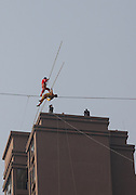 """NEIJIANG, CHINA - China Out - Finland Out<br /> <br /> Adili Wuxor, a heir of Uygur national minority tradition sports Dawaz art, performs Dawaz well known as Rope Walking between two buildings at Han'an Road in Neijiang, Sichuan Province of China. Wuxor is has been dubbed the """"Prince of tightrope walking"""" by Chinese media. <br /> ©Exclusivepix"""