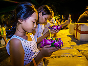 "03 NOVEMBER 2017 - BANGKOK, THAILAND:  A girl prays before floating a krathong during Loi Krathong near Wat Prayurawongsawat on the Thonburi side of the Chao Phraya River. Loi Krathong is translated as ""to float (Loi) a basket (Krathong)"", and comes from the tradition of making krathong or buoyant, decorated baskets, which are then floated on a river to make merit. On the night of the full moon of the 12th lunar month (usually November), Thais launch their krathong on a river, canal or a pond, making a wish as they do so. Loi Krathong is also celebrated in other Theravada Buddhist countries like Myanmar, where it is called the Tazaungdaing Festival, and Cambodia, where it is called Bon Om Tuk.    PHOTO BY JACK KURTZ"