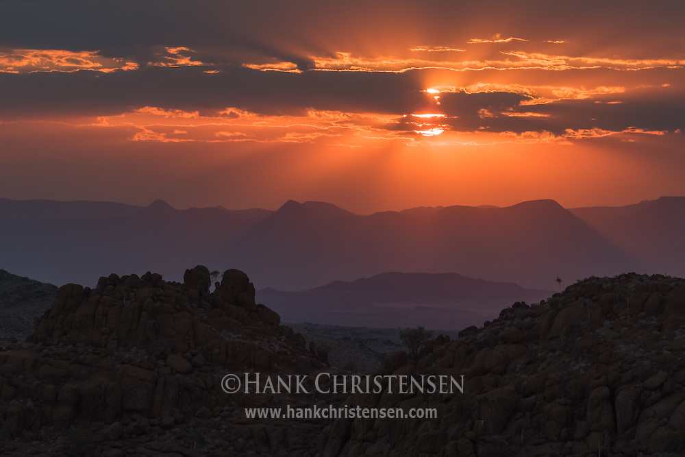 Godrays stretch out from the sun setting over the African desert region of Damaraland, Twyfelfontein, Namibia.