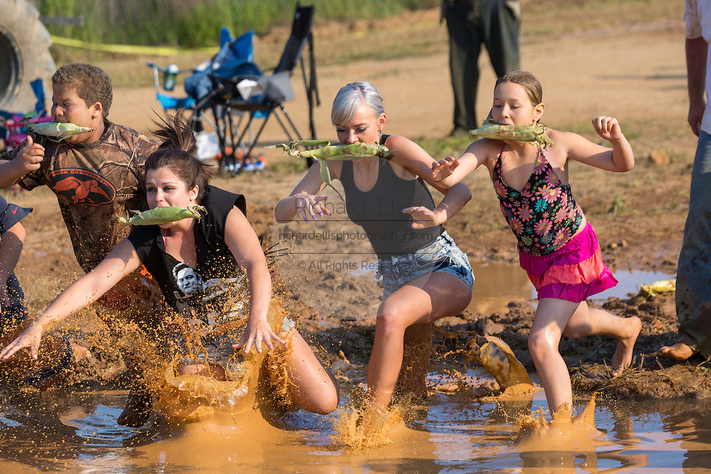 Brittney Austin from the Reality TV show Myrtle Manor jumps into muddy watering hole during a race at the 2015 National Red Neck Championships May 2, 2015 in Augusta, Georgia. Hundreds of people joined in a day of country sport and activities.