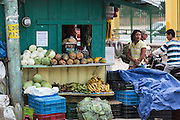 A woman stands next to a food store in the town of Valle de Angeles, Honduras on Friday April 26, 2013.
