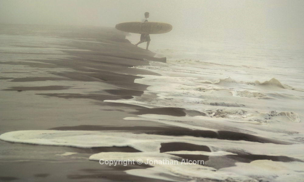 Ocean water washes on shore during hight tide as a surfer walks out for a surf session on a foggy morning on Venice Beach