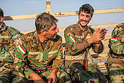 Peshmerga break out in song during a truck ride to a nearby irrigation canal for a late Friday afternoon swim. Near the Mount Batiwa frontline. Iraqi Kurdistan.