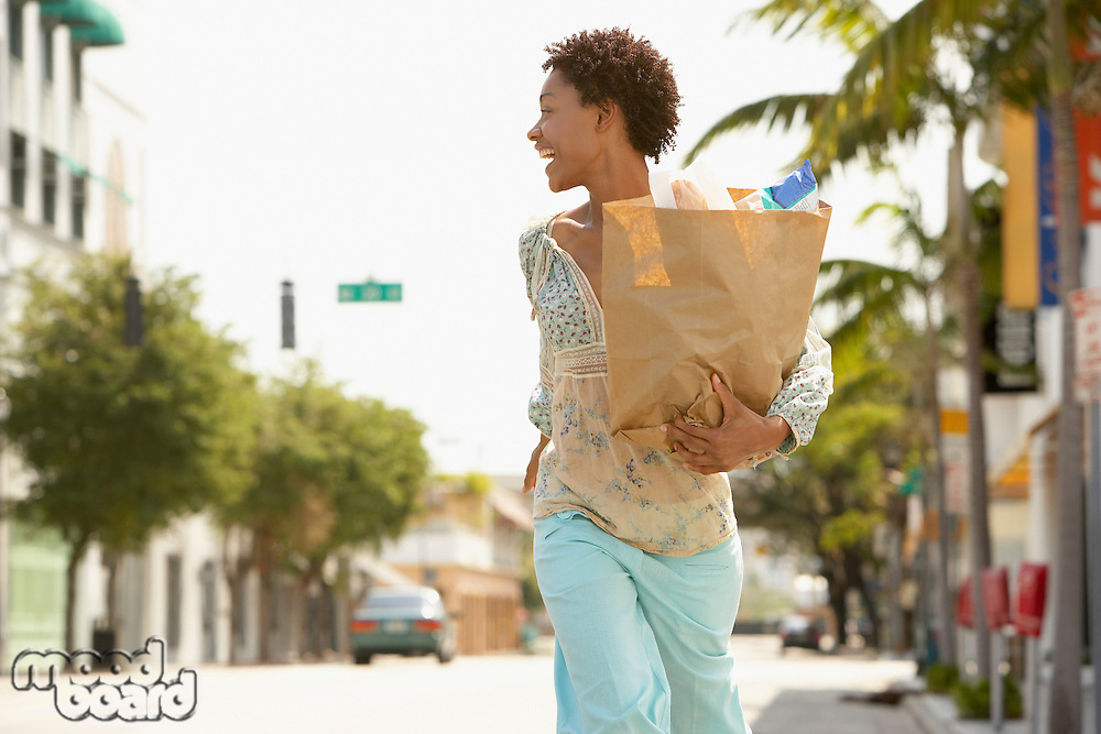 Woman carrying grocery bag while walking profile