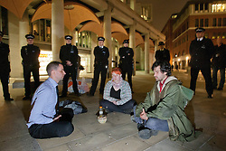 © licensed to London News Pictures. London, UK 01/05/2012. Protesters meditating while they are surrounded by police officers at Paternoster Square as Occupy London activists occupy parts of the London Stock Exchange and Paternoster Square as part of May Day protests in London. Photo credit: Tolga Akmen/LNP