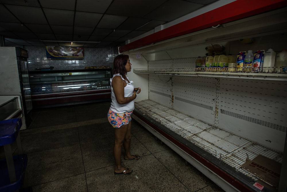 LA VELA, VENEZUELA - SEPTEMBER 22, 2016: Maria Pi&ntilde;ero shows visiting journalists an empty freezer at her local grocery store.  To escape the crisis, Ms. Pi&ntilde;ero spent all of her savings to pay smugglers to take her in a small fishing boat to Curacao island. &ldquo;I&rsquo;m nervous,&rdquo; she began. &ldquo;I&rsquo;m leaving with nothing. But I have to do this. Otherwise, we will just die here hungry.&rdquo;<br />
