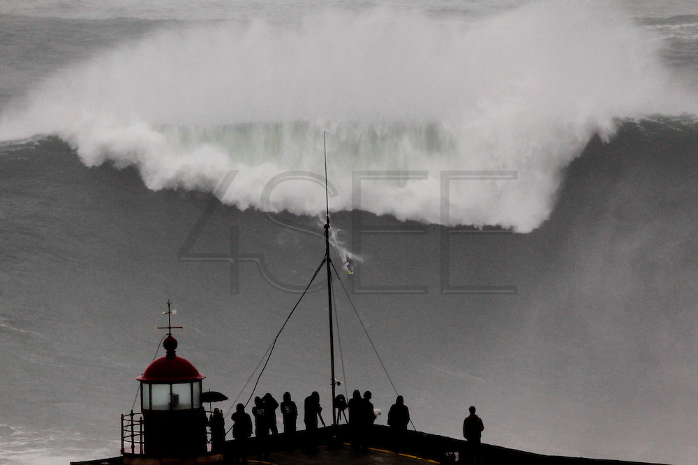 Brazilian surfer Carlos Burle surfs the tallest wave of the day at North Beach during a giant swell that hit the Portuguese coast today at Nazare, Center of Portugal, 28 October 2013. Havaiian Garrett Mcnamara's set the record for the biggest wave ever surfed on January 2013 also at Nazaré. PAULO CUNHA /4SEE