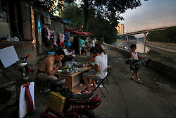A picture made available on 30 July 2013 of Chinese residents having dinner outside their home in a slum or shanty town area by the second ring road of Beijing, metres away from the prosperous Central Business District (CBD), separated only by a busy highway in China, 29 July 2013. Beijing announced plans to spend 500 billion yuan (61.5 billion euros) to renovate shanty towns within the fourth ring road according to local media. The five-year plan is expected to affect more than 230,000 households. China's massive urbanization push has resulted in the creation of large pockets of shanty towns and slums in urban areas as millions of migrant workers shifting to the cities are often priced out of city-centre properties. Slum or shanty town dwellers often live in dirty and cramped conditions, where they have no running water in their homes and have to share toilet and shower facilities.