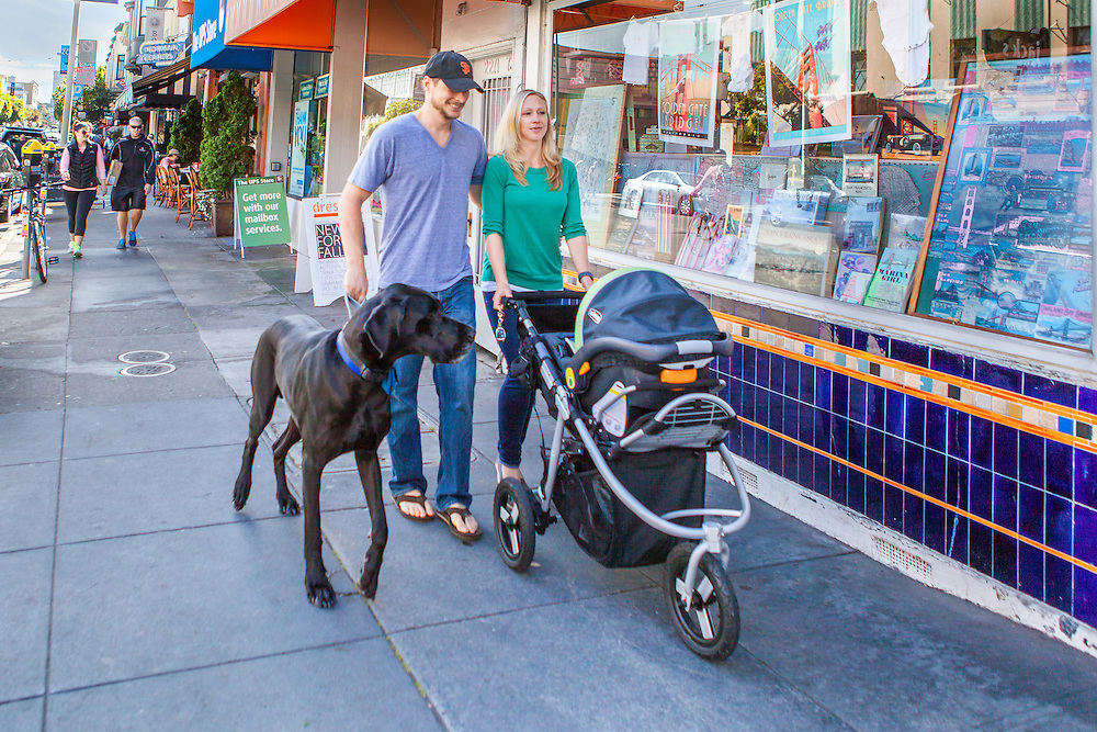 Lifestyle & Editorial Photography for CARMAnation.com. New parents walking with stroller and Great Dane on an urban street, shopping and smiling.