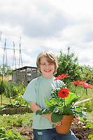 Boy holding flowers in garden