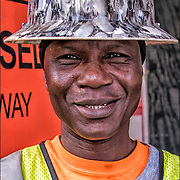 Smiling portrait of Emmanuel a West Africa blue collar worker with yellow hard hat looking into the camera.