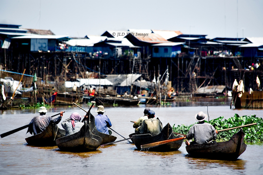 Six boatmen paddle their canoes homeward to their stilt village near the shores of Tonle Sap lake, Cambodia.  They are seen from behind, the tight row of tall homes on the shore beyond.