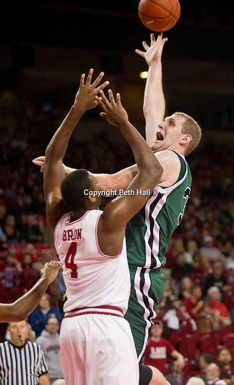 Nov 22, 2011; Fayetteville, AR, USA; Utah State Wolverines center Ben Aird (34) takes a shot over Arkansas Razorback forward Devonta Abron (4) during the second half of a game at Bud Walton Arena.  Arkansas defeated Utah 67-59. Mandatory Credit: Beth Hall-US PRESSWIRE