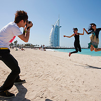 United Arab Emirates, Dubai, Two Japanese tourists jump for snapshots on Jumeirah Beach near Burj al-Arab Hotel