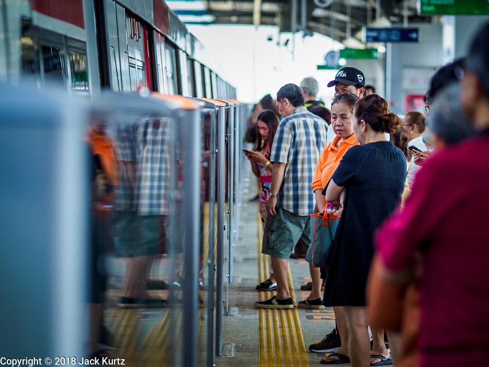 06 DECEMBER 2018 - SAMUT PRAKAN, THAILAND:  People wait for the BTS Skytrain in Kheha station. The 12.6 kilometer (7.8 miles) east extension of the Sukhumvit Line of the Bangkok BTS Skytrain opened today. The system is now 51 kilometers long (32 miles), including the 12.6 kilometer extension that opened 06 December. About 900,000 people per day use the BTS.       PHOTO BY JACK KURTZ