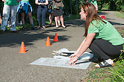 Megan Buskirk, environmental strategies coordinator for Athens City-County Health Department, demonstrates to volunteers how they will be painting mile markers on the HockHocking Adena Bikeway. © Ohio University / Photo by Kaitlin Owens