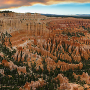 Bryce Canyon, well known for crimson-colored hoodoos, is truly a spectacle to see.  I was worried as I ventured up the mountain, there there was a vast wild fire miles up wind that cast a shadow as far as the eye could see.  When I made it to the optimal venue the smoke helped to accent the sunset, almost as if the fire set to the sky as well.