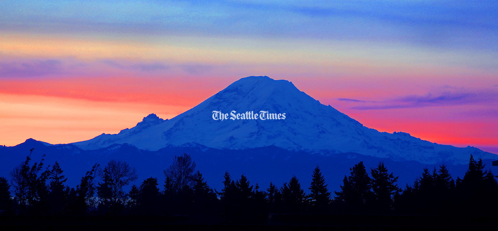 Mount Rainier looms in front of the sunrise in this view from SeaTac. (Mike Siegel / The Seattle Times)
