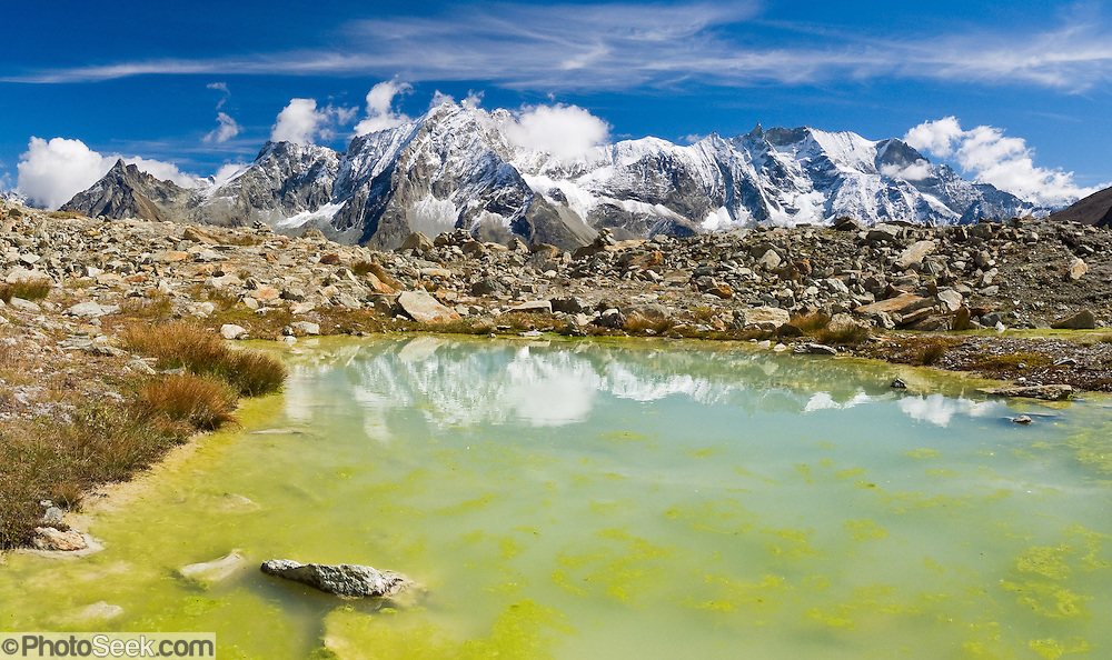 "Bright yellow algae grows in a tarn (mountain pond) which reflects peaks of Dents des Veisivi (left) and Aiguilles de la Tsa (right) above Arolla Valley, part of Val d'Hérens, in Valais (Wallis) Canton, Switzerland, Europe. Hike the High Route (Chamonix-Zermatt Haute Route) for classic mountain scenery. Panorama stitched from 3 images. Published in ""Light Travel: Photography on the Go"" book by Tom Dempsey 2009, 2010. Published in Ryder-Walker Alpine Adventures ""Inn to Inn Alpine Hiking Adventures"" Catalog 2006-2009, 2011-12."