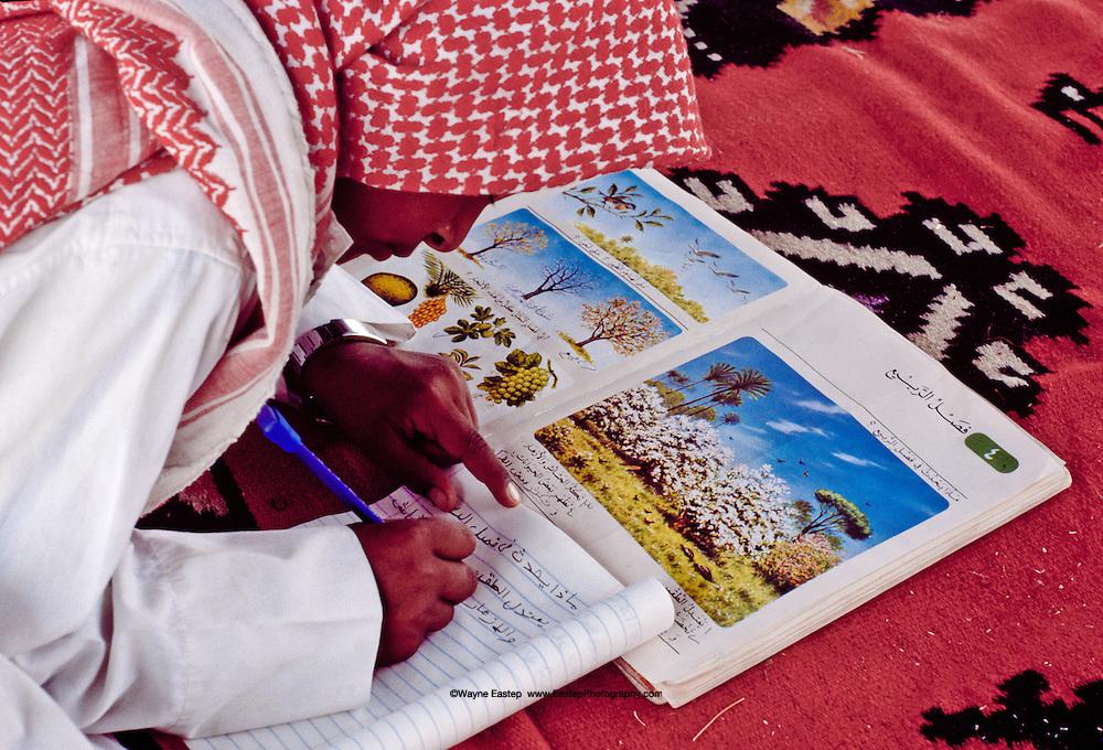 Young Al Amrah boy doing his homework at desert encampment in the Dahana Sands, Saudi Arabia.