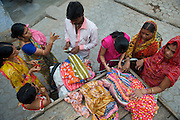 A cycling street seller bargains with group of women over Sari prices.