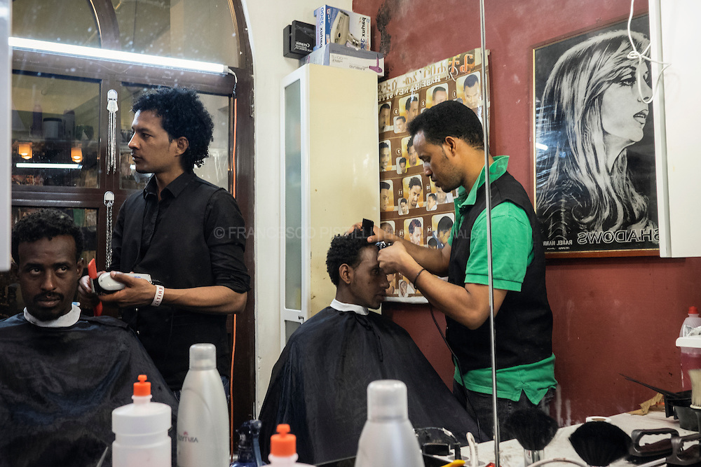 A volunteering barber shop inside the Baobab building. After months traveling thru the deserts and seas, this two Eritrean  hairdressers cut migrants' hair to give them dignity and prevent an outbreak of head lice.