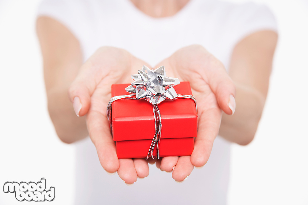 Woman offering small gift mid section close-up on hands