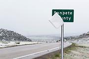 Snow slab sliding off Sanpete County sign along Highway 28 in Central Utah.
