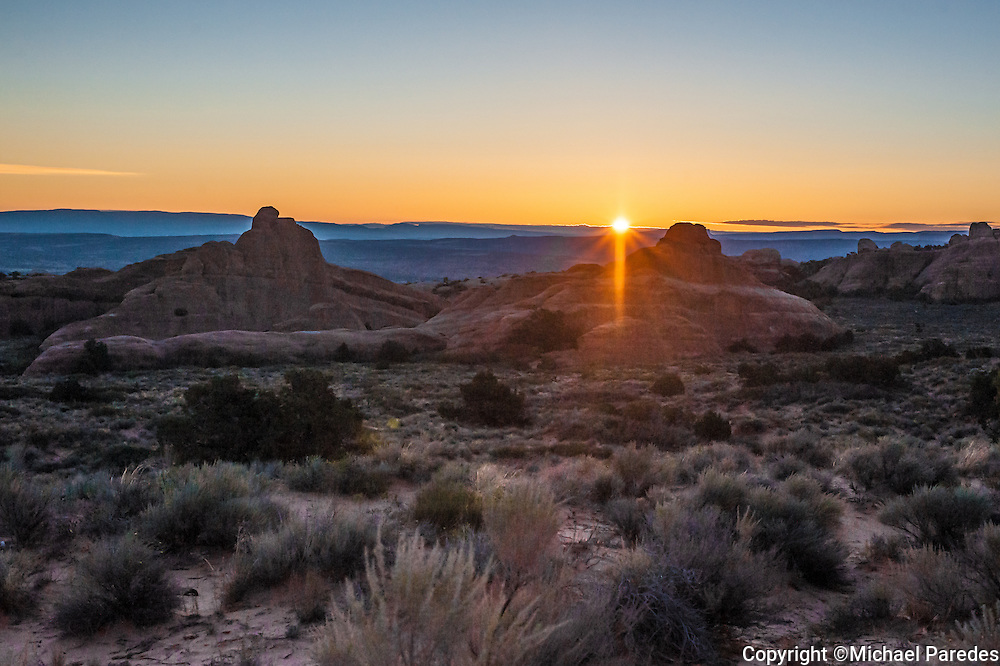 Sun sets in a blueish blend of mountains and cloud at Arches National Park, Utah.