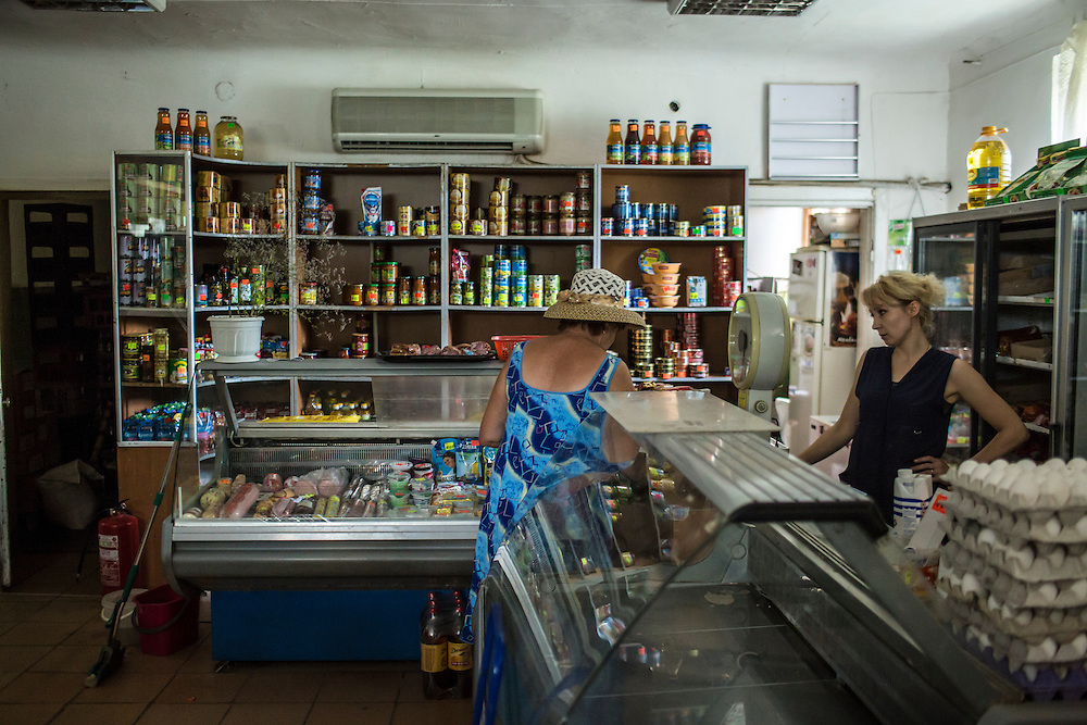 A resident of the Ploshchadka neighborhood, which has been heavily bombarded in recent days, shops at a local store in which the electricity has been cut on Wednesday, July 30, 2014 in Donetsk, Ukraine.