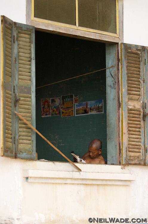 A Buddhist monk reads by an open window near Kratie, Cambodia.