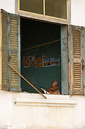 A Buddhist monk reads by an open window near Kratie, Cambodia.