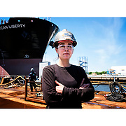 """Samantha Toggas, Temple graduate and apprentice welder at the Philadelphia shipyard in front of the project tanker ship """"American Freedom,"""" the 27th ship built at the yard. ED HILLE / Staff Photographer"""