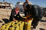 Rafah, Gaza.  Men trade gasoline imported from Egypt through the tunnels along the Gaza border in the popular Star Market. Propane gas, gasoline, diesel, motorcycles, washer machines, generators, many goods and even animals for local zoos pass through this tunnels.   After the devastating  Israeli military campaign known as Operation Cast Lead, and several bombing raids, goods are still passing to the palestinian side.  The conflict resulted in between 1,166 and 1,417 Palestinian and 13 Israeli deaths (4 from friendly fire).    (PHOTO: MIGUEL JUAREZ LUGO)