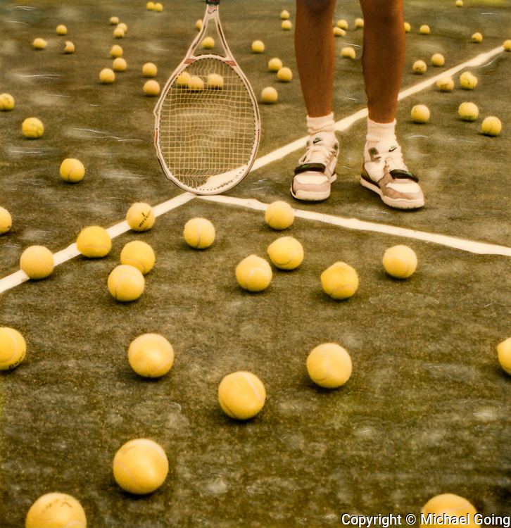 Altered Polaroid SX-70 photo of tennis court full of tennis balls with tennis players feet and racquet