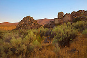 Diffused golden light at sunrise colors the high desert landscape and rock outcroppings in the Mormon Basin of Malheur County, Oregon.