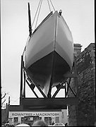 "The ""Asgard "" at Kilmainham Jail..1979..01.04.1979..04.01.1979..1st April 1979..The historic yacht ""Asgard"" owned by Erskine Childers was brought to Kilmainham Jail,Dublin. The vessel had to be hoisted ,by crane,over the outer wall of the jail. It was placed as part of a future exhibition to be set up by The National Museum..Image shows the yacht lift in progress."