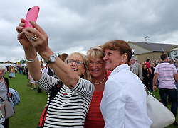 © Licensed to London News Pictures.14/07/15<br /> Harrogate, UK. <br /> <br /> Three women take a selfie during the visit of HRH The Prince of Wales and the Duchess of Cornwall on the opening day of the Great Yorkshire Show.  <br /> <br /> England's premier agricultural show opened it's gates today for the start of three days of showcasing the best in British farming and the countryside.<br /> <br /> The event, which attracts over 130,000 visitors each year displays the cream of the country's livestock and offers numerous displays and events giving the chance for visitors to see many different countryside activities.<br /> <br /> Photo credit : Ian Forsyth/LNP