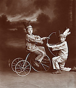 Vintage Photo Two boys in Indian costumes one with bow and arrow, the other on a tricycle with a pistol, circa 1900