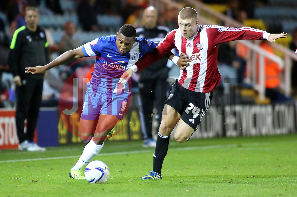 Peterborough United's Britt Assombalonga in action with Brentford's Jake Bidwell - Photo mandatory by-line: Joe Dent/JMP - Tel: Mobile: 07966 386802 08/10/2013 - SPORT - FOOTBALL - London Road Stadium - Peterborough - Peterborough United V Brentford - Johnstone's Paint Trophy