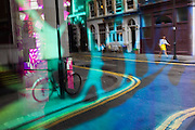 Seen through the abstract coloured mirrored glass of a backstreet bar, a lady passer-by in similar colour to the double-yellow lines