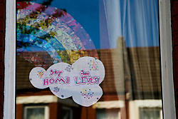 © Licensed to London News Pictures. 15/04/2020. London, UK. Hand painted rainbow and 'STAY HOME' signs are displayed in a window of a house in north London. Coronavirus lockdown continues to slow the spread of COVID-19 and reduce pressure on the NHS. Photo credit: Dinendra Haria/LNP
