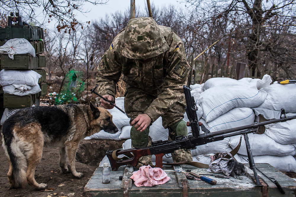 PIKSY, UKRAINE - NOVEMBER 19, 2014: A member of the Dnipro-1 brigade, a pro-Ukraine militia, cleans his gun in Pisky, Ukraine. The village of Pisky is the scene of much of the front-line fighting over the Donetsk airport. CREDIT: Brendan Hoffman for The New York Times