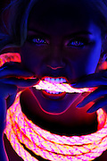Portrait of a woman biting on a glowing rope.Black light
