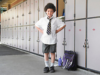 Elementary schoolboy standing by school lockers portrait